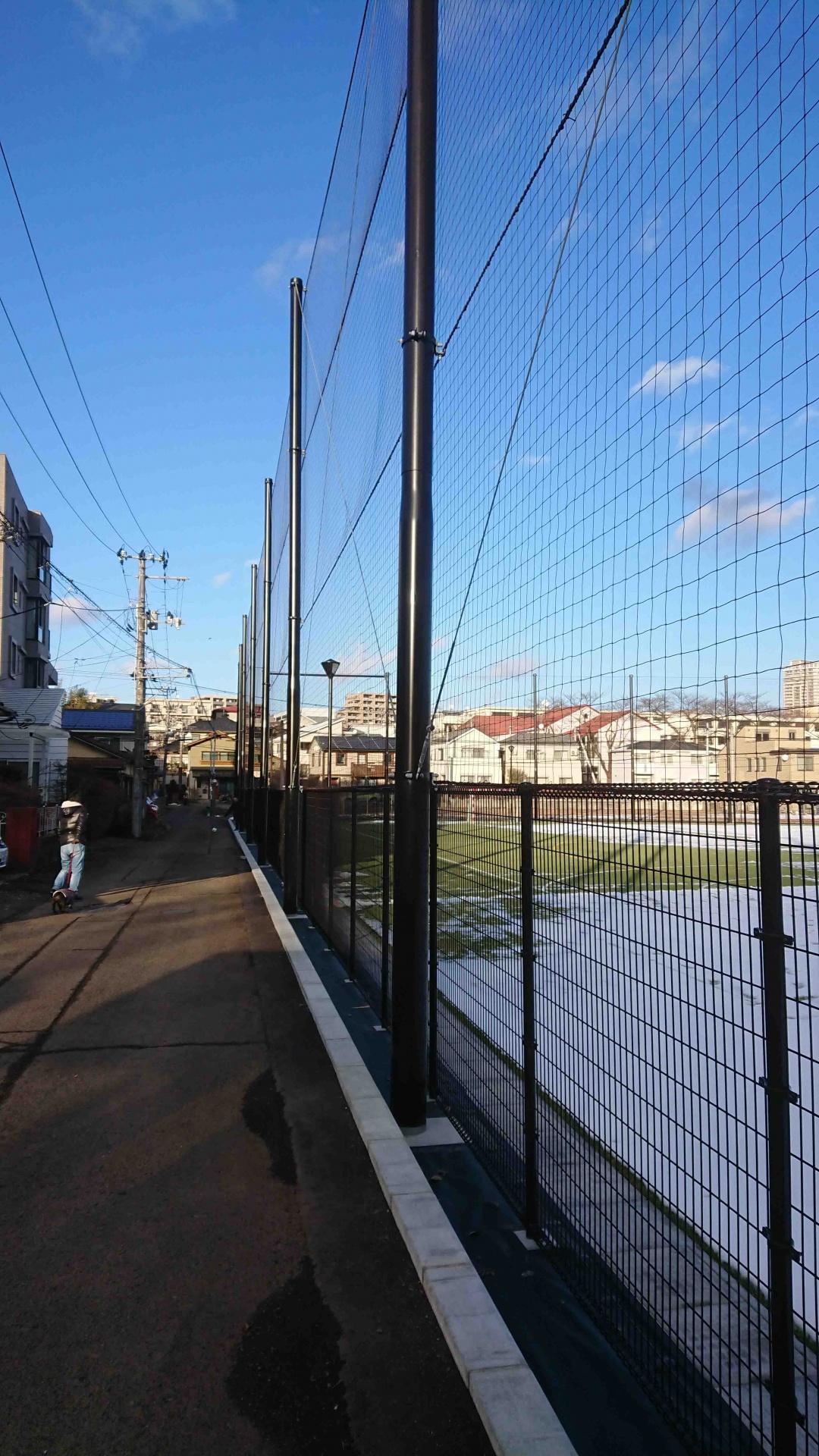 図5 グラウンド東西北面を取り囲む柵(高さ10m超)と照明搭(高さ5m超),2021/01/11撮影