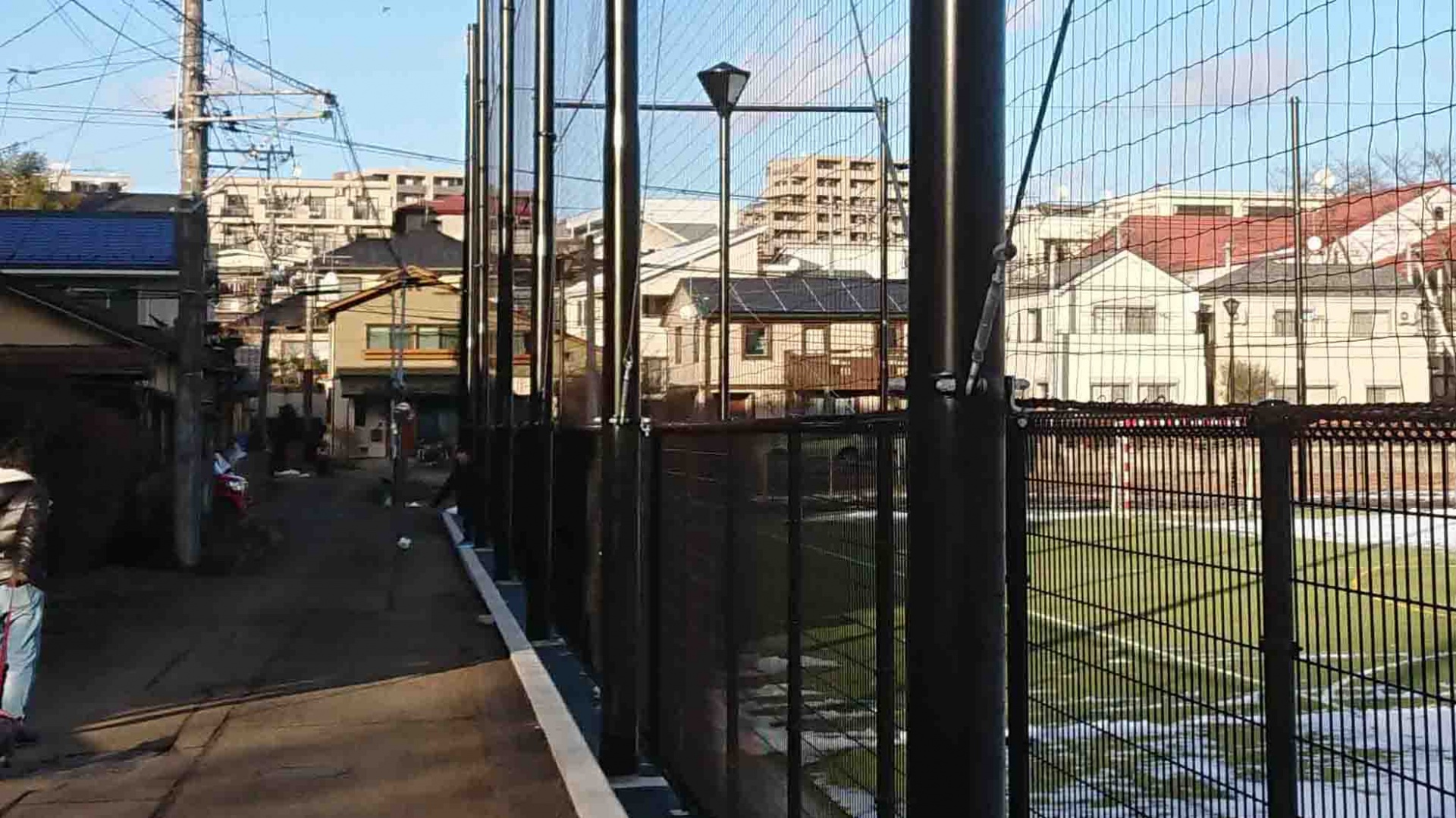 グラウンド敷地内に設置された照明灯,公共スペース側に光が漏れないように遮光板が設けられている