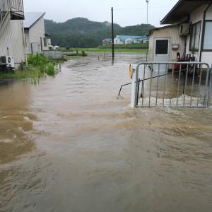 川の洪水と道路冠水